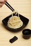 Spaghetti macaroni in black ceramic plate with chopsticks at bam. Spaghetti macaroni taking from black ceramic dish by chopsticks at light bamboo mat background Stock Images