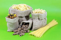 Spaghetti and Macaroni of Different Shapes and Colors in Jute Bag  on Green Royalty Free Stock Images