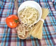 Spaghetti, macaroni en tomaat op stof Stock Afbeeldingen
