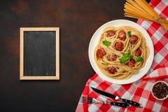 Spaghetti makaron z klopsikami, czereśniowy pomidorowy kumberland, talerz kreda na ośniedziałym tle, obrazy royalty free