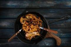 spaghetti Makaron z owoce morza na gorącej smaży niecce z łyżką i rozwidleniem na barwionym drewnianym tle Odgórny widok zdjęcia royalty free