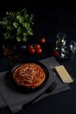Spaghetti makaron z pomidorowym kumberlandem, świeżym pomidorem i serem na ciemnym tle, Obraz Royalty Free
