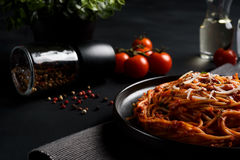 Spaghetti makaron z pomidorowym kumberlandem, świeżym pomidorem i serem na ciemnym tle, obraz stock