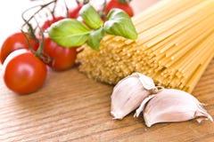 Spaghetti makaron z słodkimi małymi pomidorami zielenieje basilu i czosnku Obraz Stock