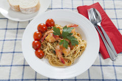 Spaghetti Marinara. Authentic Italian spaghetti marinara with fresh prawns, cherry tomatoes and bread Stock Images