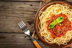 Spaghetti with marinara sauce. Italian cuisine. Lunch or dinner. A serving of spaghetti pasta with tomato marinara sauce and basil on a dark wooden table. Copy stock images