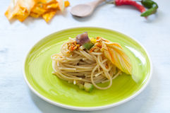 Spaghetti with marinated anchovy, zucchini and zucchini flowers. Italy royalty free stock images