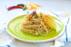 Spaghetti with marinated anchovy, zucchini and zucchini flowers. Italy royalty free stock image