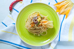 Spaghetti with marinated anchovy, zucchini and zucchini flowers. Italy stock photo
