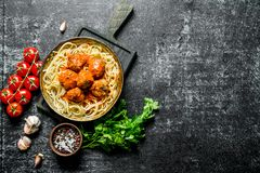 Spaghetti and meat balls in pan with parsley, tomatoes and garlic stock photos