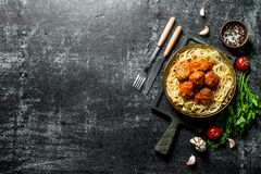 Spaghetti and meat balls in pan with spices, herbs and tomatoes royalty free stock images