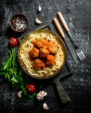 Spaghetti and meat balls in pan with spices, herbs and tomatoes. On rustic background stock photography