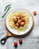 Spaghetti with meat balls on a plate of rosemary and tomatoes royalty free stock photography