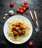 Spaghetti and meat balls on a plate with tomatoes and garlic stock image