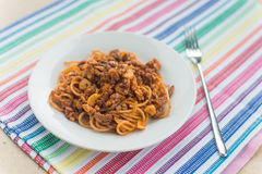 Spaghetti with meat in the white plate. On the colored napkin Royalty Free Stock Photos