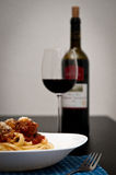 Spaghetti meatball dish. With tomato sauce and a glass of red wine in the background Royalty Free Stock Photography