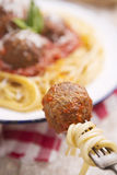 Spaghetti and meatball on a fork, plate in the background Stock Photos