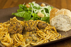 Spaghetti and Meatballs. A meal of spaghetti and meatballs, with a side salad and bread Royalty Free Stock Image