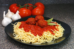 Spaghetti and Meatballs. Plate of spaghetti and meatballs with tomatoes and garlic in background Royalty Free Stock Photography