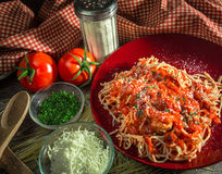 Spaghetti And Meatballs Dinner. Parmesan cheese, oregano, paprika, and mozzarella cheese surround a plate of spaghetti and meatballs with a red and white gingham Royalty Free Stock Images