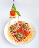 Spaghetti with meatballs, some on fork. One serving of spaghetti with meatballs in tomato sauce and some spaghetti with sauce and basil on a fork royalty free stock image