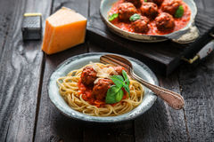 Spaghetti with meatballs and tomato sauce and basil, rustic style, selective focus Royalty Free Stock Photography