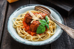 Spaghetti with meatballs and tomato sauce and basil, rustic style, selective focus Royalty Free Stock Photos