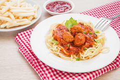 Spaghetti with meatballs in tomato sauce and french fries Royalty Free Stock Image