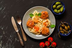 Spaghetti with meatballs in tomato sauce served in a gray plate, capers, olives, tomatoes. Black concrete background, top view. stock images