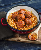 Spaghetti and meatballs in tomato sauce on wooden rustic board. Royalty Free Stock Photography