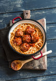Spaghetti and meatballs in tomato sauce on wooden rustic board. Stock Photography