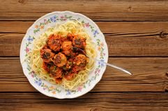 Spaghetti with meatballs in tomato sause on wooden table Royalty Free Stock Image