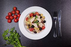 Spaghetti with tuna, capers, olives, Sicilian chilli pepper, cherry tomatoes and a sprinkling of parsley. Spaghetti with Mediterranean tuna, capers, olives Stock Photography