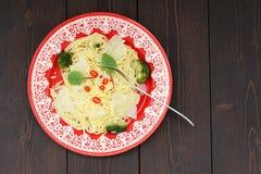 Spaghetti met aardappels, broccoli, Spaanse peper en snijbiet in rode plaat Stock Afbeelding