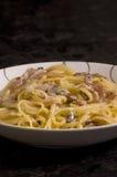 Spaghetti met bacon en paddestoelsaus Stock Afbeeldingen