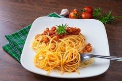 Spaghetti met saus in de schotel op de houten lijst stock afbeeldingen