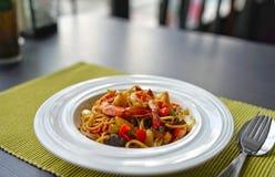 Spaghetti met Thaise Kruidige Kruidensaus en garnalen op witte plaat Stock Afbeeldingen