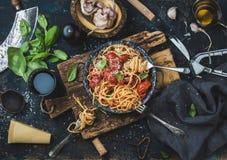 Spaghetti met tomaat en basilicum en ingrediënten voor het maken van deegwaren royalty-vrije stock afbeelding