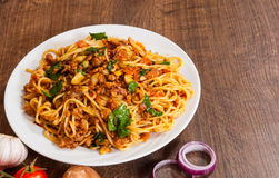 Spaghetti with mushroom, vegetables and minced meat. In a plate on wooden table Stock Images