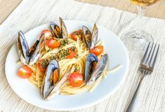 Spaghetti with mussels and cherry tomatoes Stock Photo
