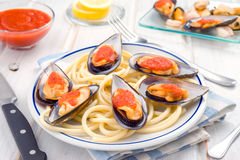 Spaghetti and mussels with tomato sauce in white china. Dish stock photos
