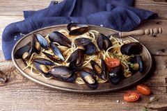 Spaghetti with mussels, tomatoes in spicy sauce in the original plate on the old wooden table. Clams Mytilus closeup. royalty free stock images