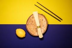 Spaghetti na drewnianym talerzu z żółtym i purpurowym tłem zdjęcie royalty free