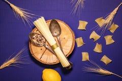 Spaghetti na drewnianym talerzu z dwa rocznik łyżkami zdjęcie royalty free
