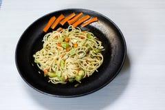 Spaghetti naczynie z warzywami, czarny naczynie, biały tło obraz royalty free