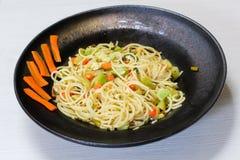 Spaghetti naczynie z warzywami, czarny naczynie, biały tło zdjęcie stock
