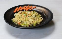 Spaghetti naczynie z warzywami, czarny naczynie, biały tło zdjęcia stock