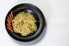 Spaghetti naczynie z warzywami, czarny naczynie, biały tło zdjęcie royalty free