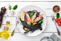 Spaghetti neri Paste nere con frutti di mare ed il limone Gamberetto e cozze Sui vecchi precedenti immagini stock libere da diritti