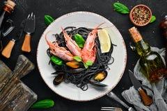 Spaghetti neri Paste nere con frutti di mare ed il limone Gamberetto e cozze Sui vecchi precedenti immagini stock